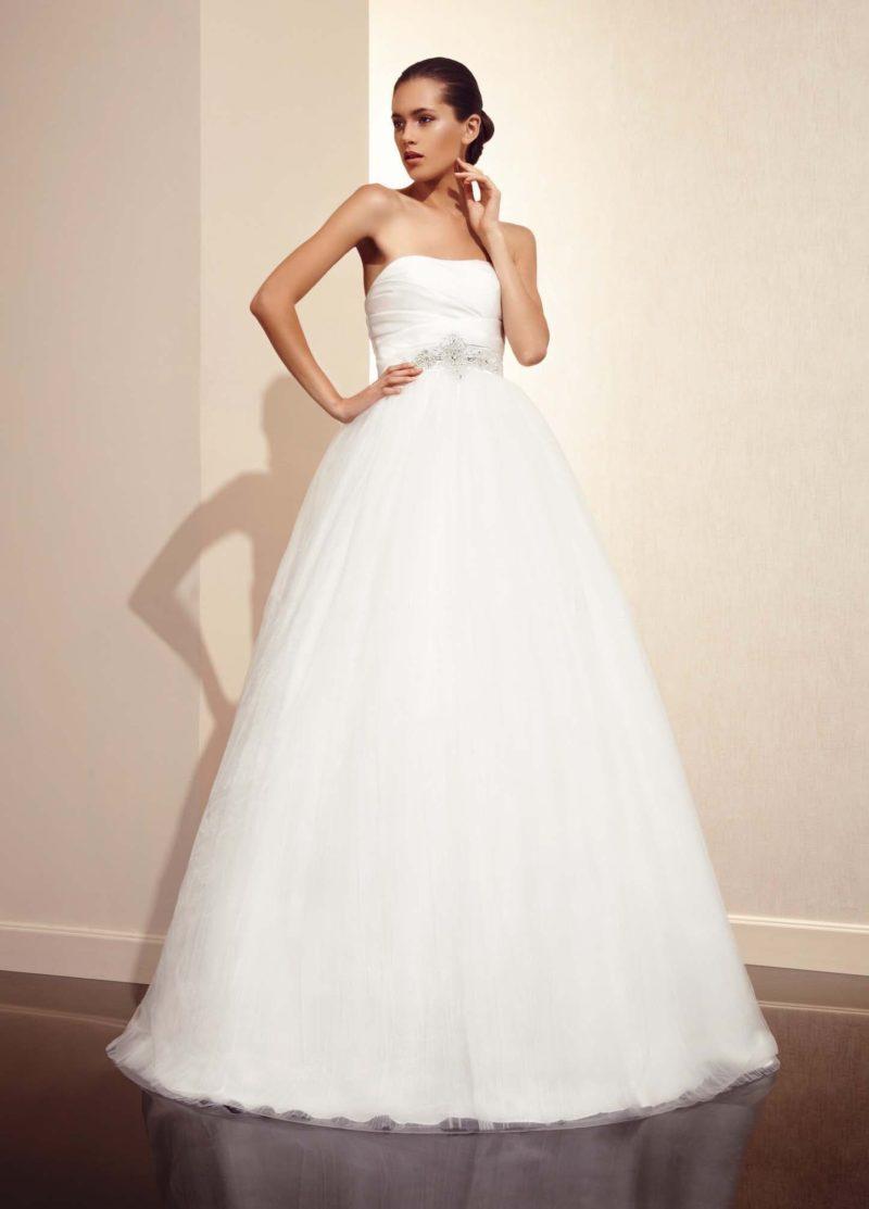 Впечатляющее свадебное платье с прямым кроем открытого лифа и многослойной юбкой.