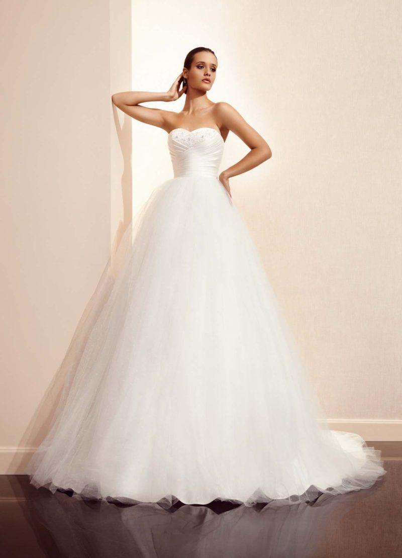 Роскошное свадебное платье с многослойной объемной юбкой со шлейфом и драпировками на корсете.