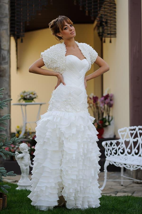 Свадебное платье с пышным декором юбки с разрезом и объемным болеро.