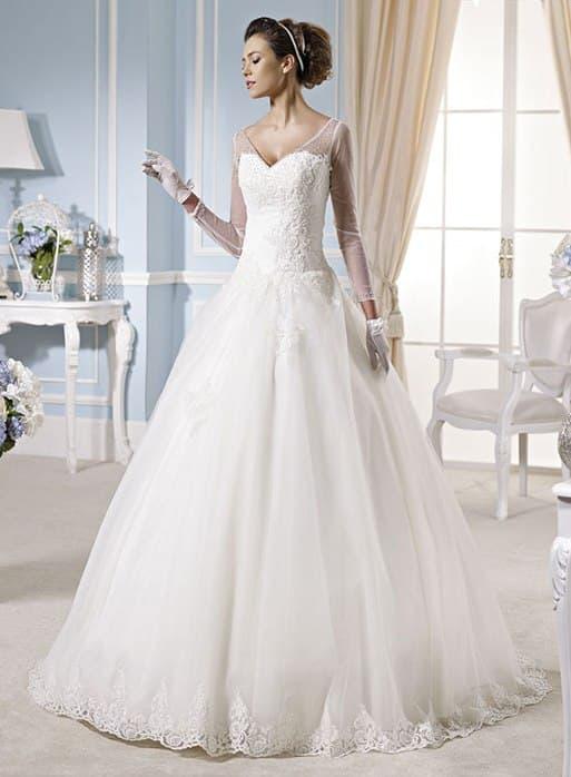 Пышное свадебное платье с V-образным вырезом, оформленным тонкой тканью.