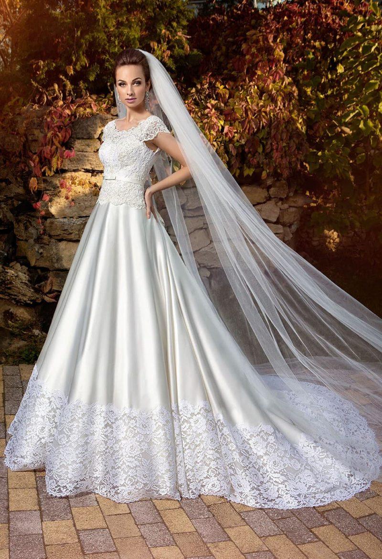 Глянцевое свадебное платье с пышной юбкой со шлейфом и кружевным декором.