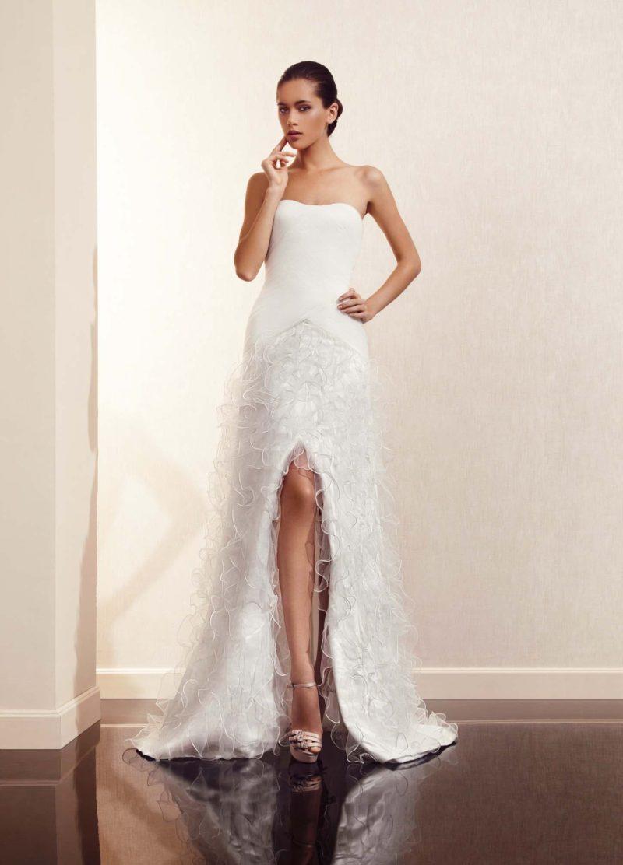 Прямое свадебное платье с открытым декольте и разрезом сбоку по подолу, украшенному оборками.