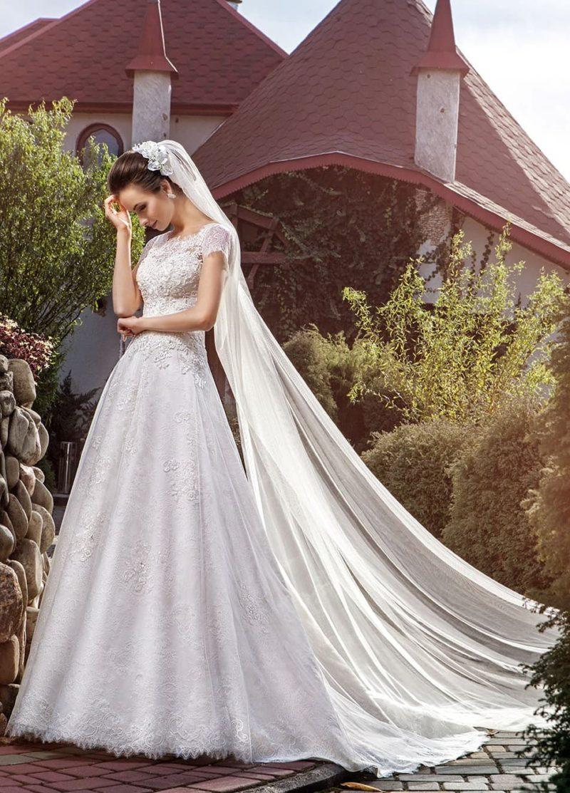 Закрытое свадебное платье с коротким кружевным рукавом и роскошным шлейфом.