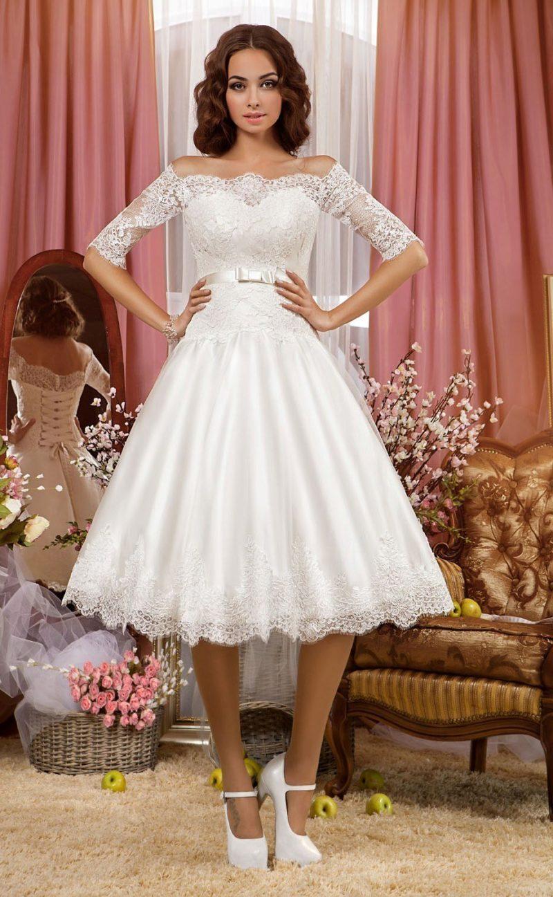 Короткое свадебное платье с кружевным рукавом и ажурным декором подола.