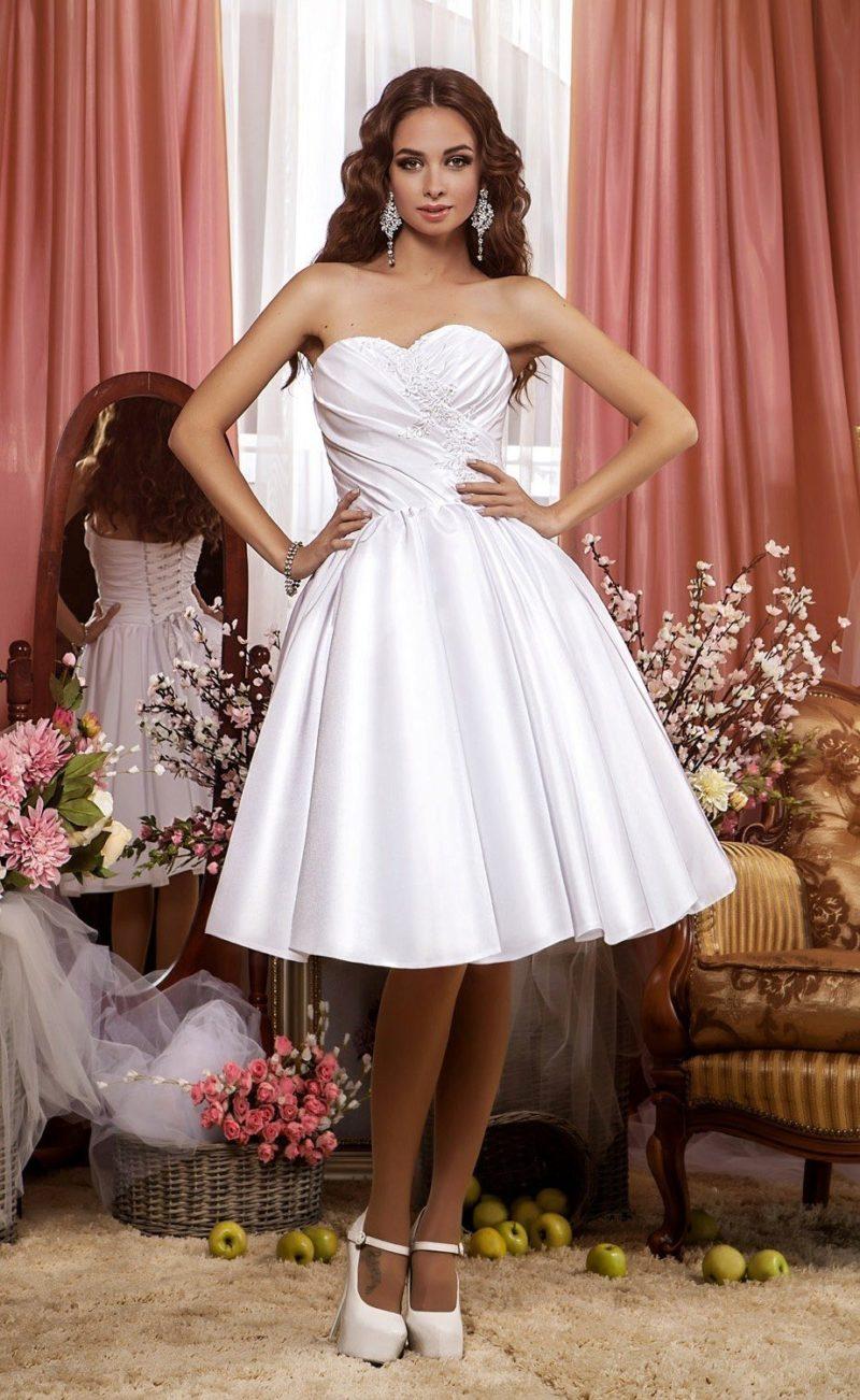 Атласное свадебное платье с декором из драпировок и юбкой до колена.