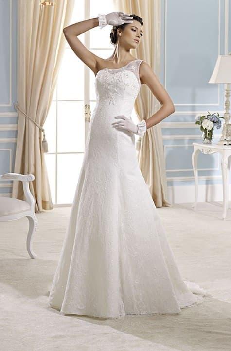 Изысканное свадебное платье облегающего кроя с полупрозрачным асимметричным верхом.