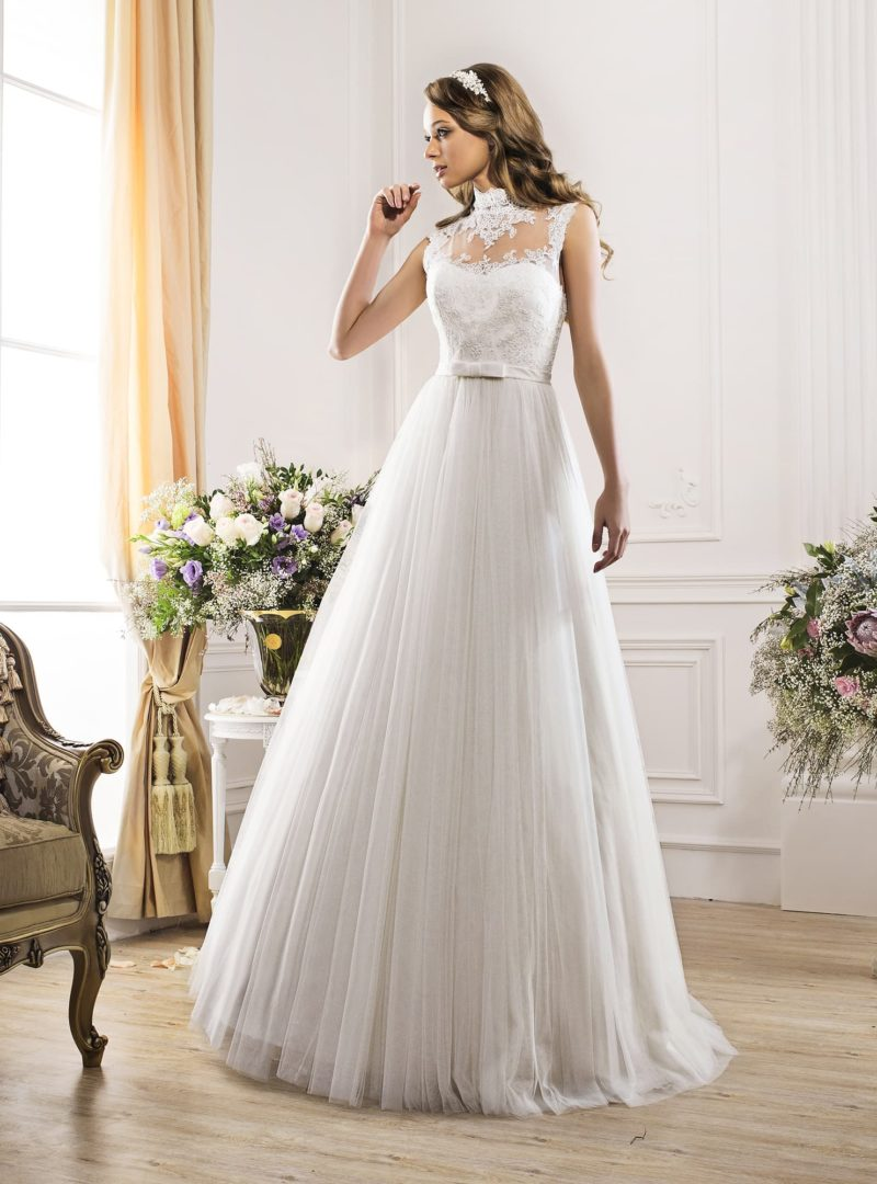 Закрытое свадебное платье с многослойной юбкой и полупрозрачным верхом с поясом.