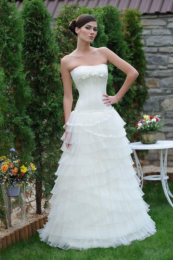 Пышное свадебное платье с причудливыми оборками и прямым декольте.