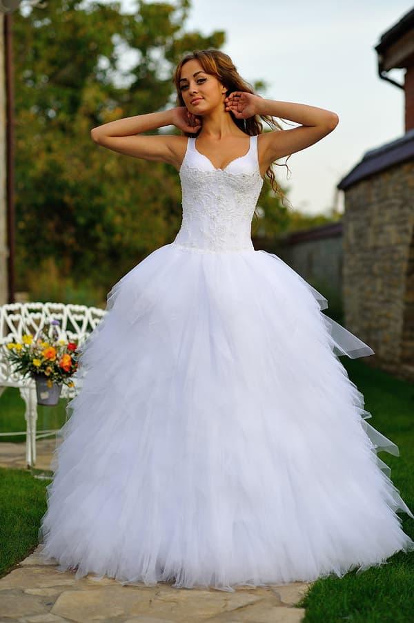 Притягательное свадебное платье с пышной юбкой из тонкой ткани и изящным вырезом.