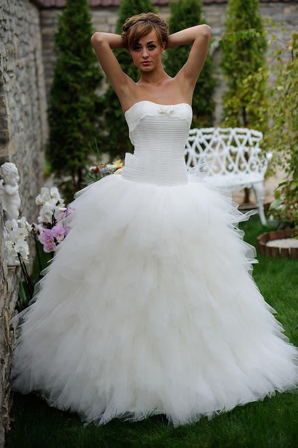 Открытое свадебное платье с многослойной юбкой, украшенной воздушными оборками.