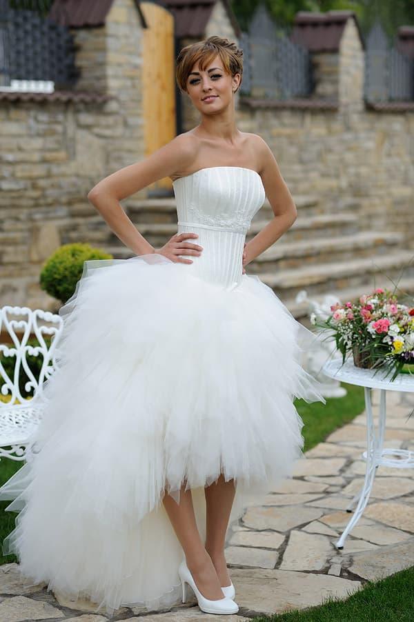 Эксцентричное свадебное платье с невероятно пышной юбкой, укороченной спереди.