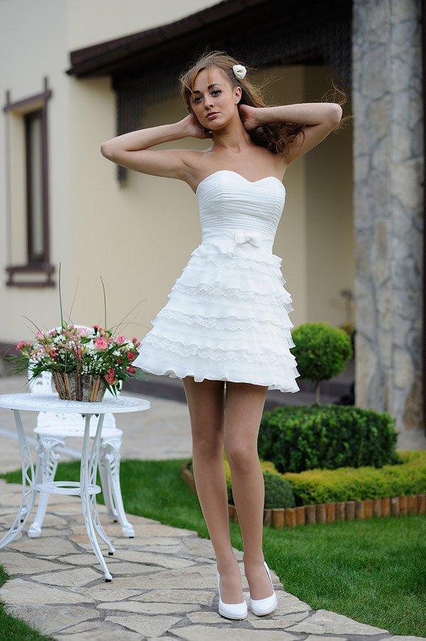Короткое свадебное платье с юбкой А-кроя и декором из складок ткани.