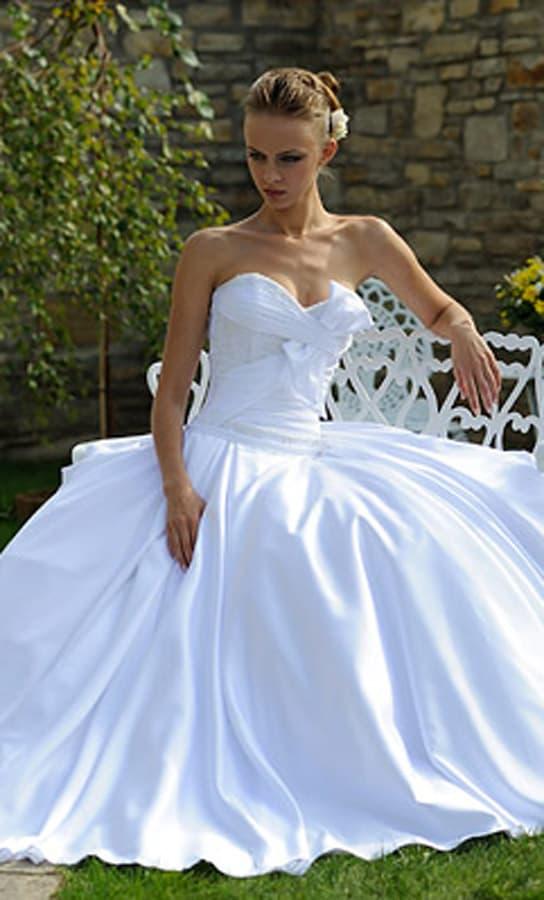 Атласное свадебное платье с роскошными волнами ткани на открытом лифе.