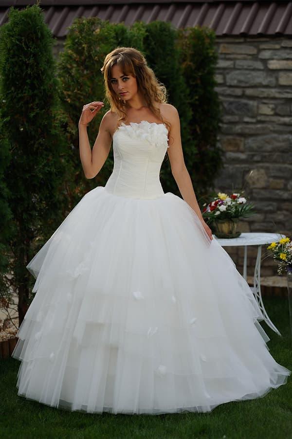 Свадебное платье с роскошной многослойной юбкой и объемным декором на лифе.