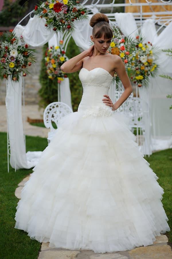 Пышное свадебное платье с декольте в форме сердца и роскошным объемным декором.