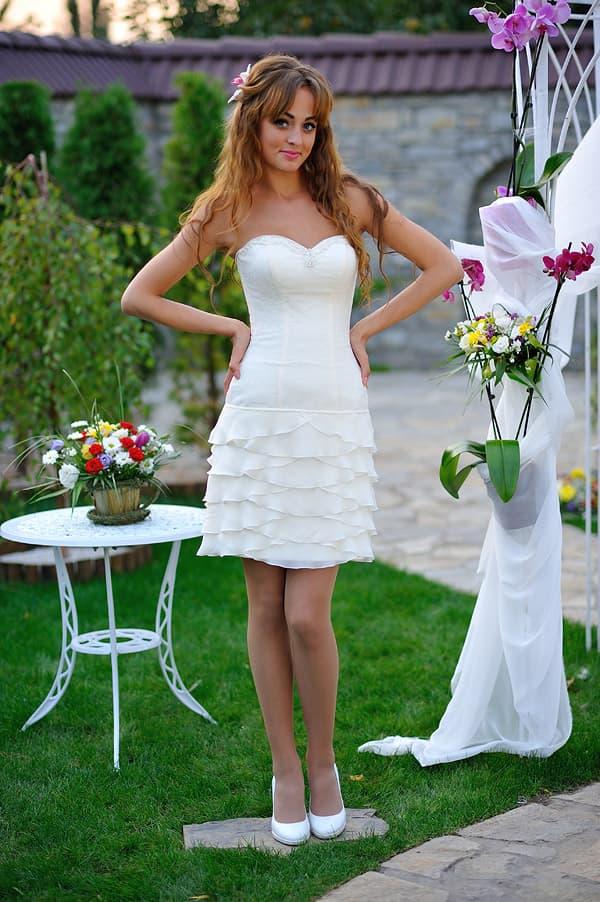 Лаконичное свадебное платье с облегающим корсетом и юбкой до колена.