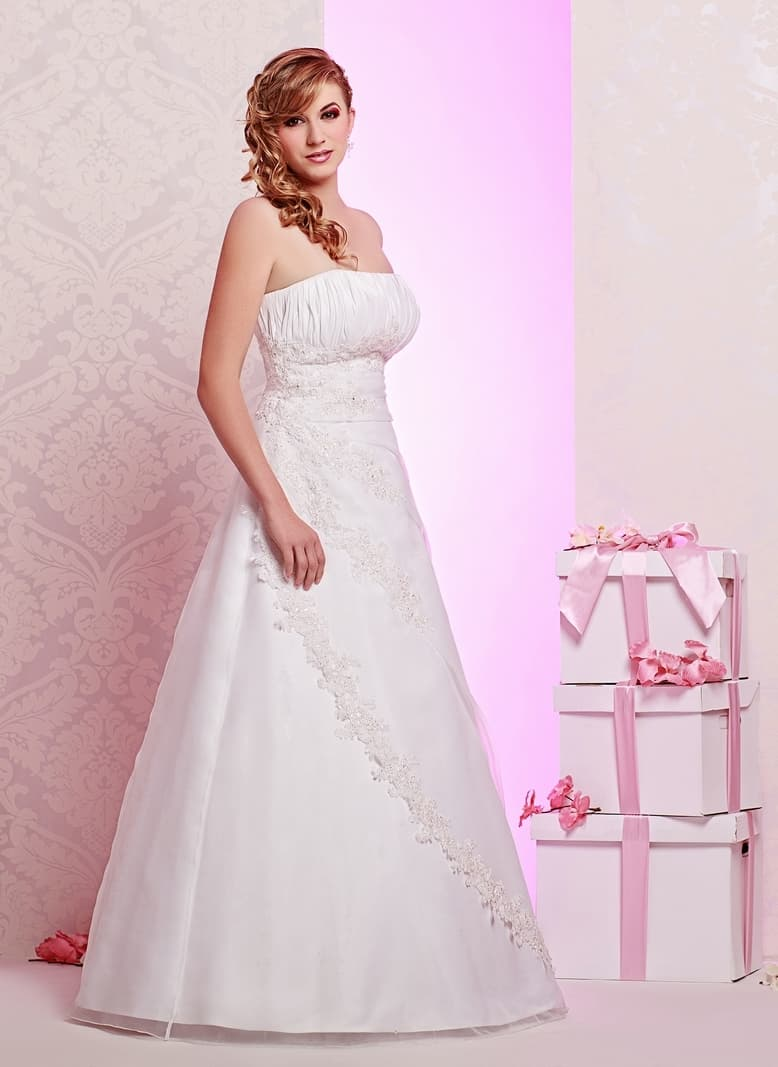 Свадебное платье с пышной юбкой и лифом прямого кроя, покрытым драпировками.