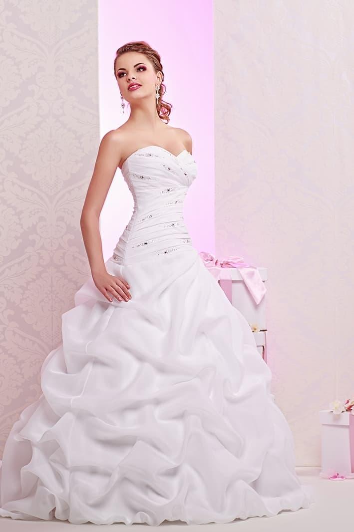 Эффектное свадебное платье с пышной отделкой подола и классическим декольте.