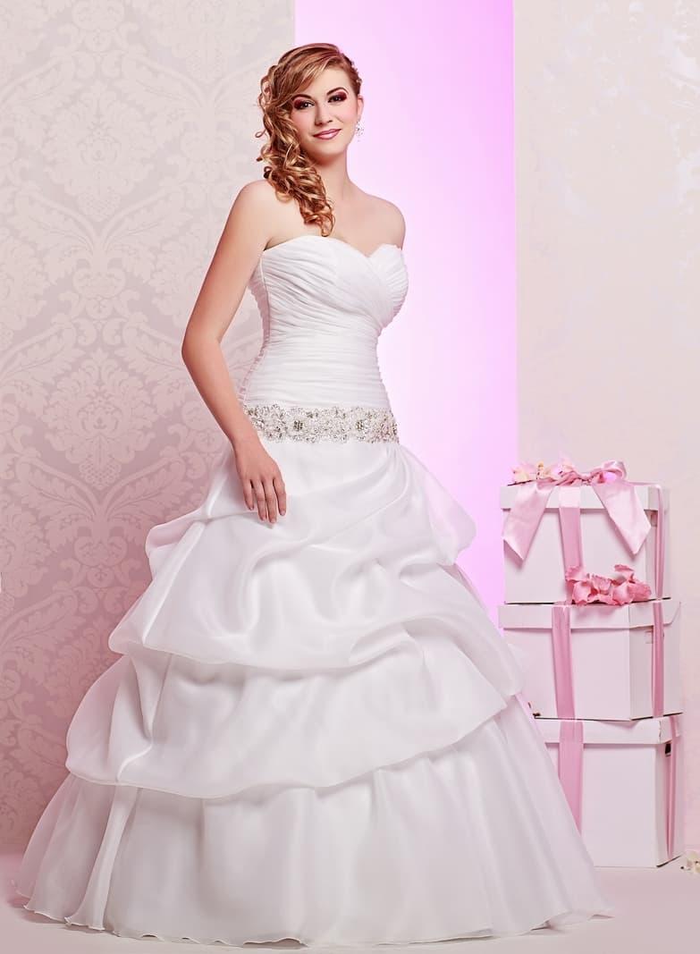 Пышное свадебное платье с объемными волнами на юбке и широким бисерным поясом.