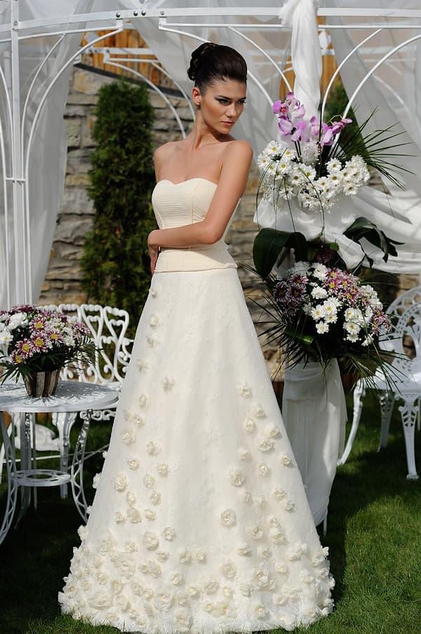 Свадебное платье с бежевым корсетом и юбкой, украшенной бутонами.