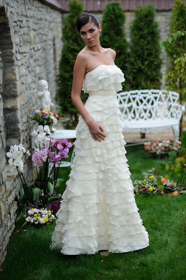 Свадебное платье цвета слоновой кости, покрытое воздушными волнами ткани.