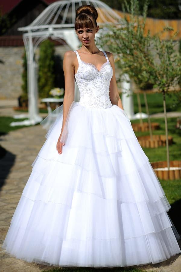 Свадебное платье с многоярусным низом и атласным лифом с узкими бретелями.