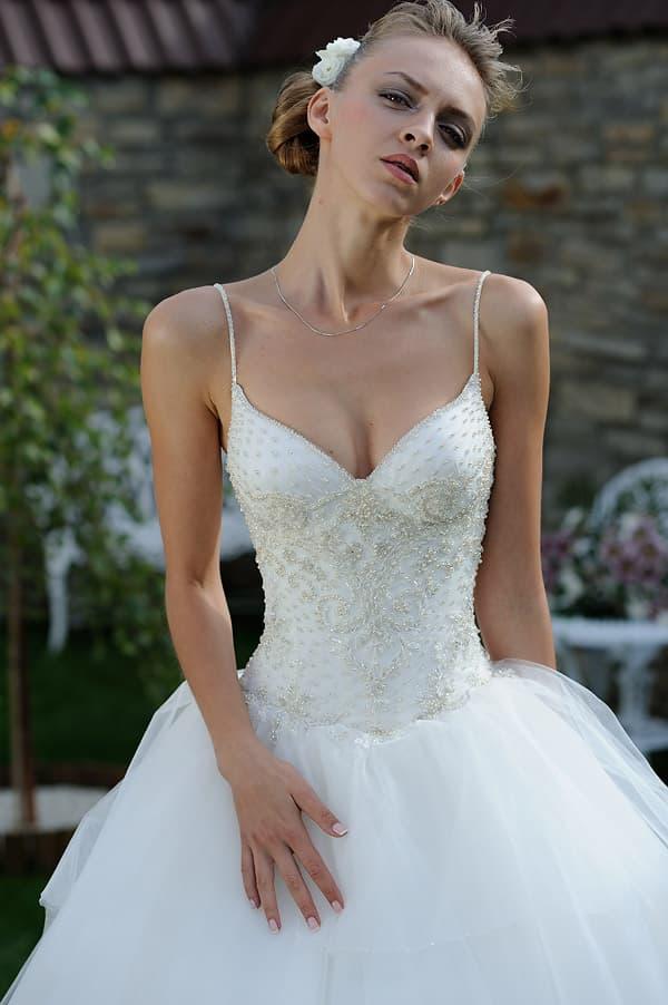Пышное свадебное платье с романтичным подолом и открытым лифом.