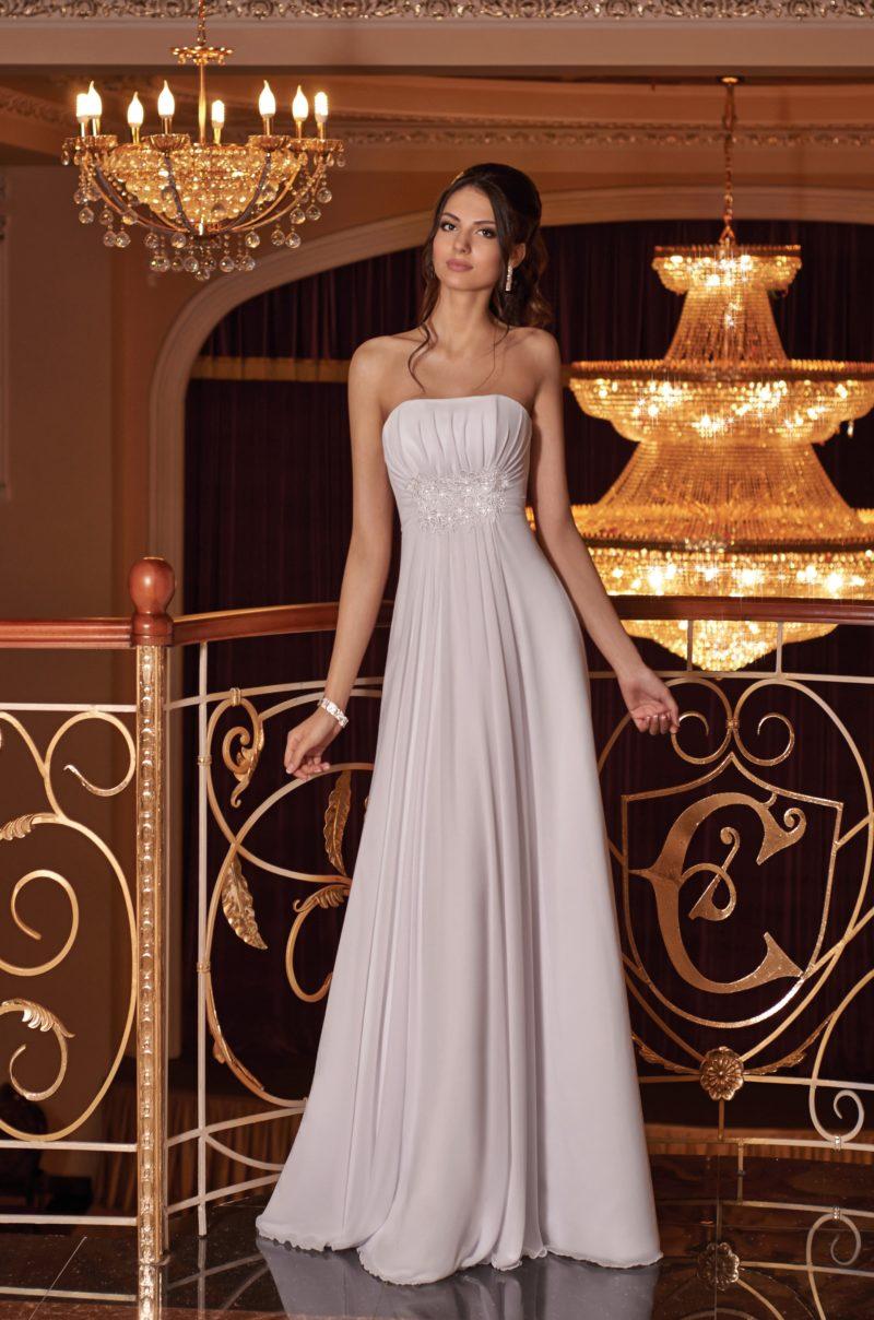 Деликатное прямое свадебное платье с волнами ткани на юбке и вышивкой на лифе.