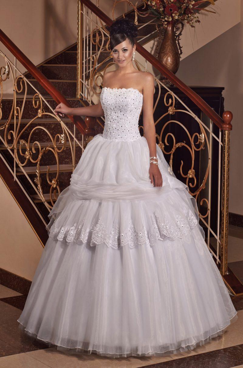 Пышное свадебное платье с необычным объемным декором подола и открытым лифом.