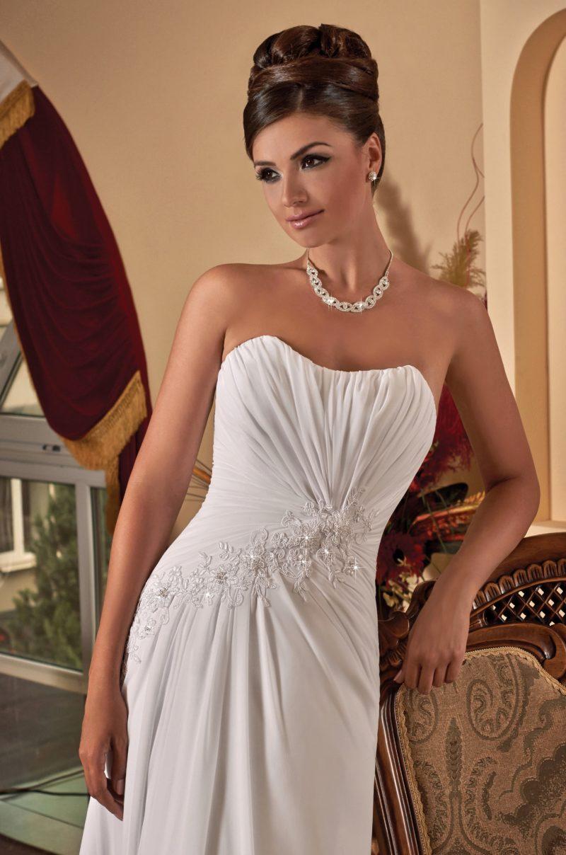Открытое свадебное платье с драпировками и кружевной отделкой облегающего корсета.
