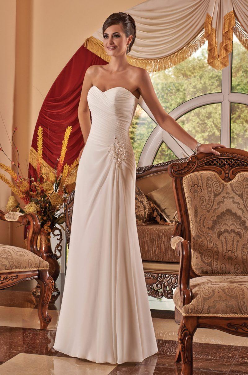 Открытое свадебное платье с лифом в форме сердца, украшенное драпировками и вышивкой.