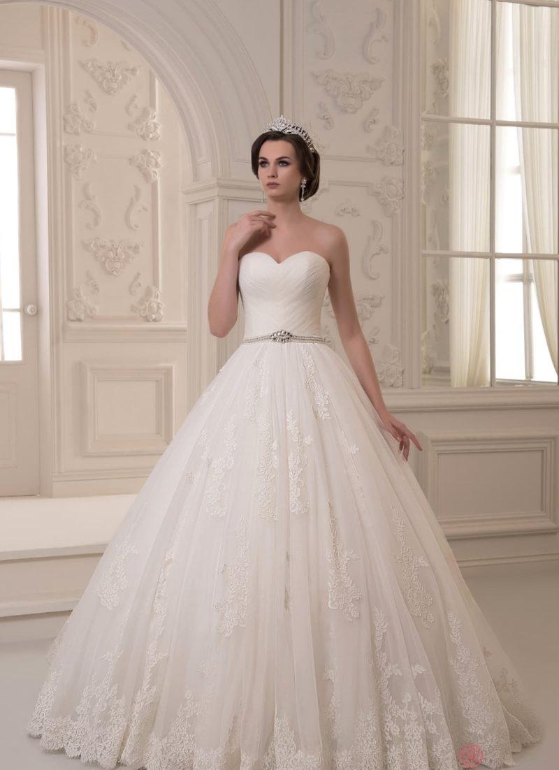 Торжественное свадебное платье с открытым лифом и юбкой, декорированной кружевами.