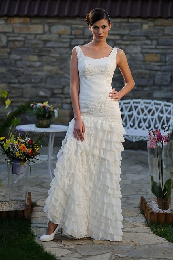 Прямое свадебное платье с небольшими оборками по всей юбке и изящным вырезом.