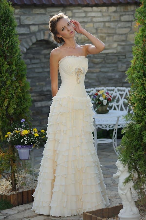 Кремовое свадебное платье с открытым лифом и многоярусными оборками на юбке.