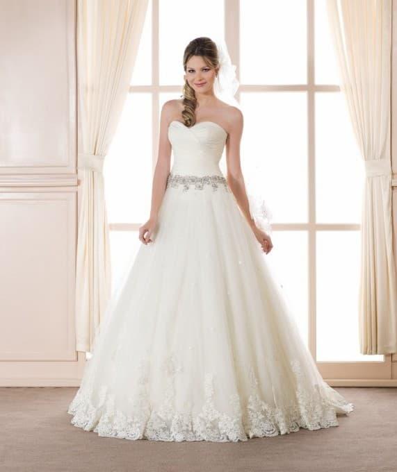 Лаконичное свадебное платье пышного кроя с кружевом по низу подола и блестящим поясом.