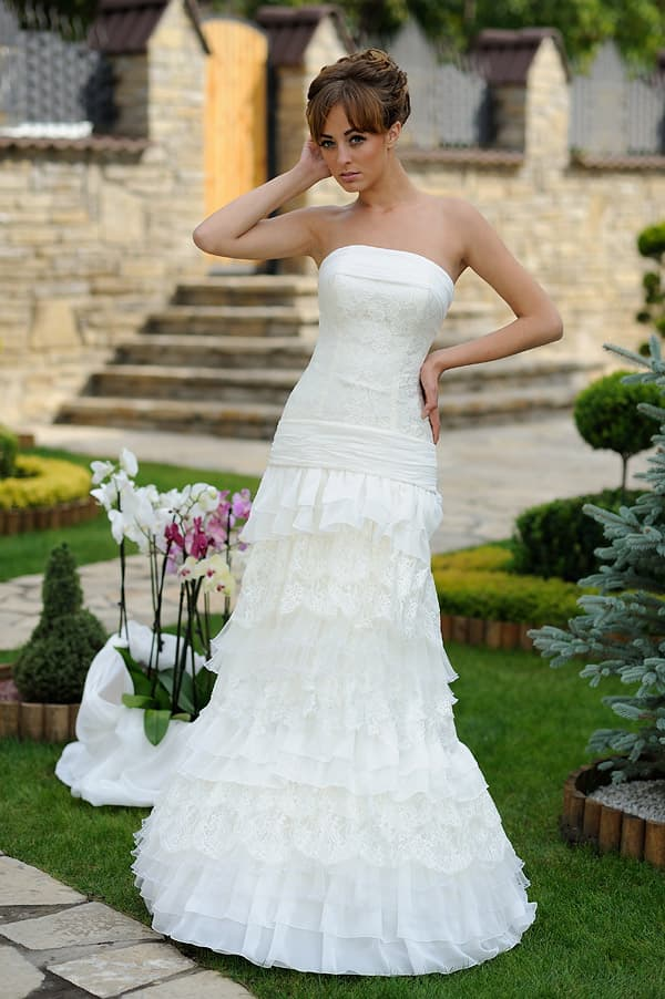 Открытое свадебное платье с кружевным корсетом и пышным декором юбки.