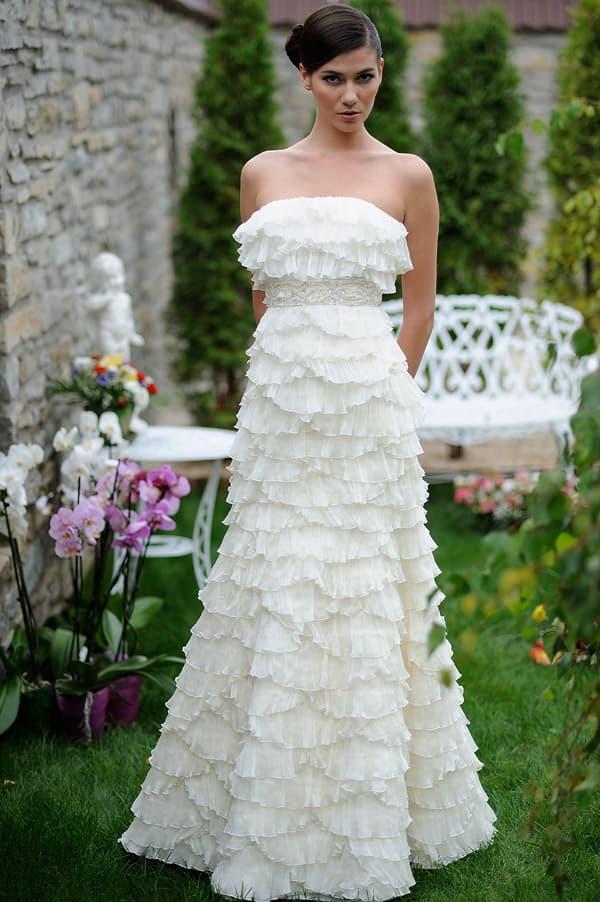 Утонченное свадебное платье, полностью покрытое легкими оборками из тонкой ткани.