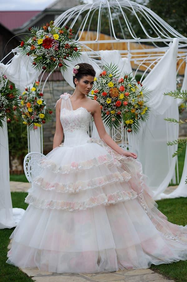 Пышное свадебное платье с розовыми оборками на юбке и асимметричным верхом.