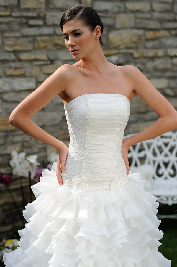 Свадебное платье с кружевом по бокам корсета и очаровательной юбкой.