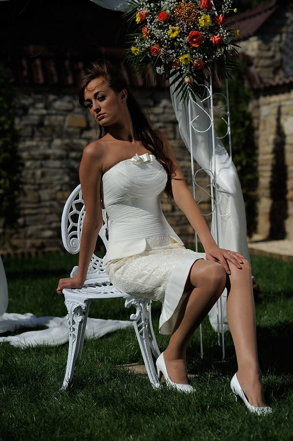 Короткое свадебное платье с кружевной юбкой и складками ткани по корсету.