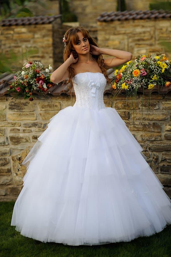 Пышное свадебное платье с небольшим бантом на открытом лифе.