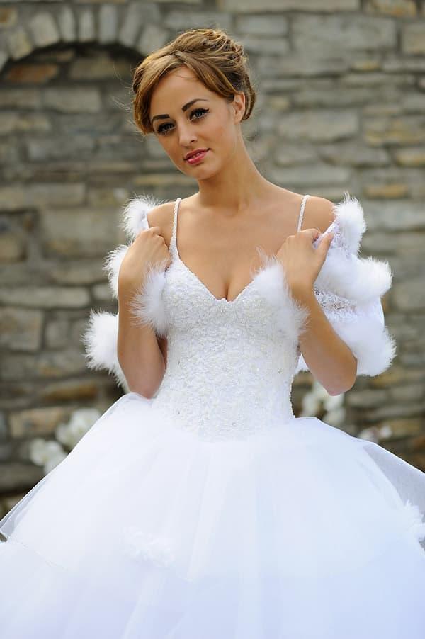 Классическое свадебное платье пышного кроя с бретелями-спагетти и болеро, украшенным перьями.