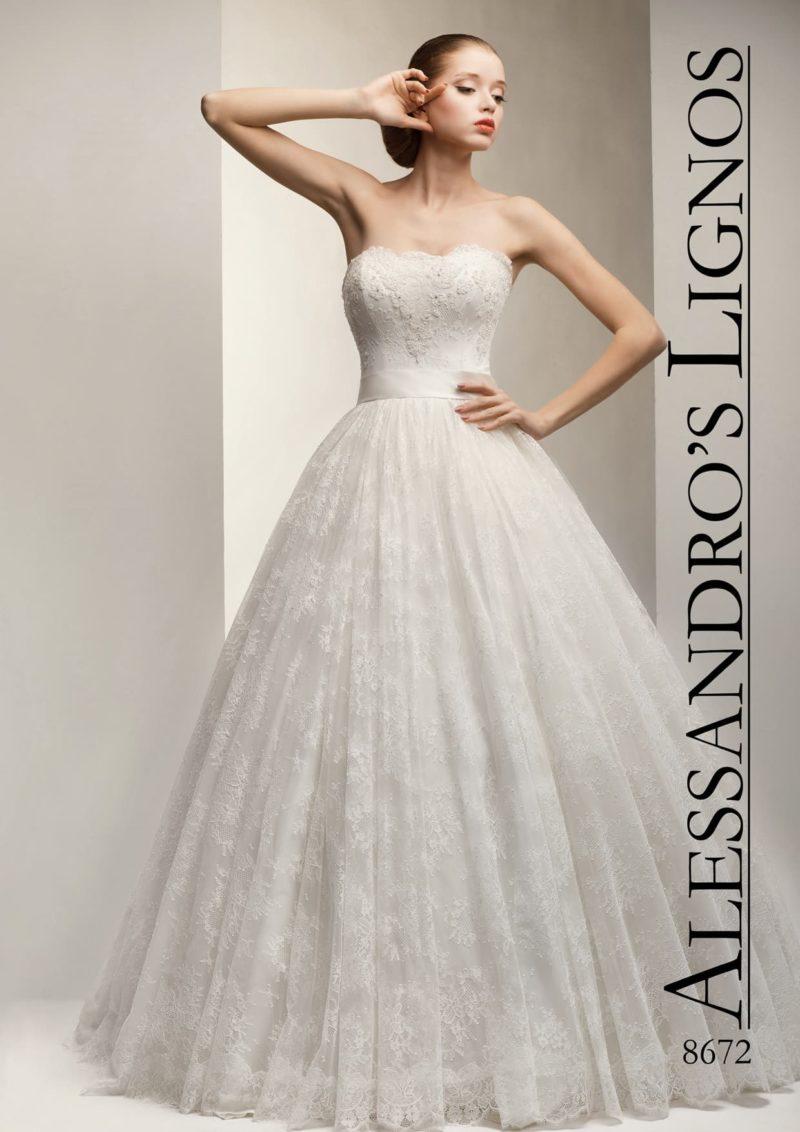 Пышное свадебное платье с кружевным верхом юбки и изящным поясом на талии.