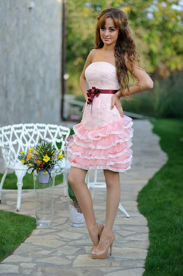 Короткое свадебное платье в розовых тонах с бордовым поясом из атласа.