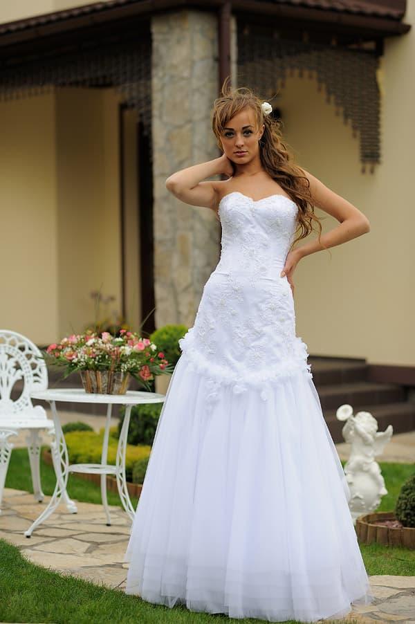 Свадебное платье с заниженной талией и декором из кружевных аппликаций.