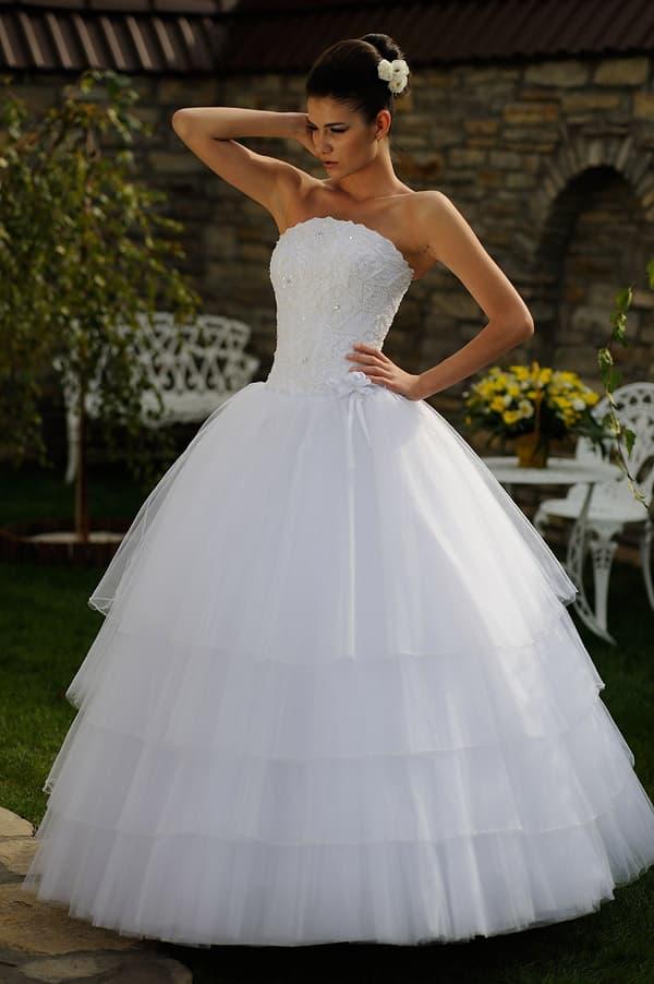 Открытое свадебное платье с многоярусным низом и корсетом, украшенным бисером.