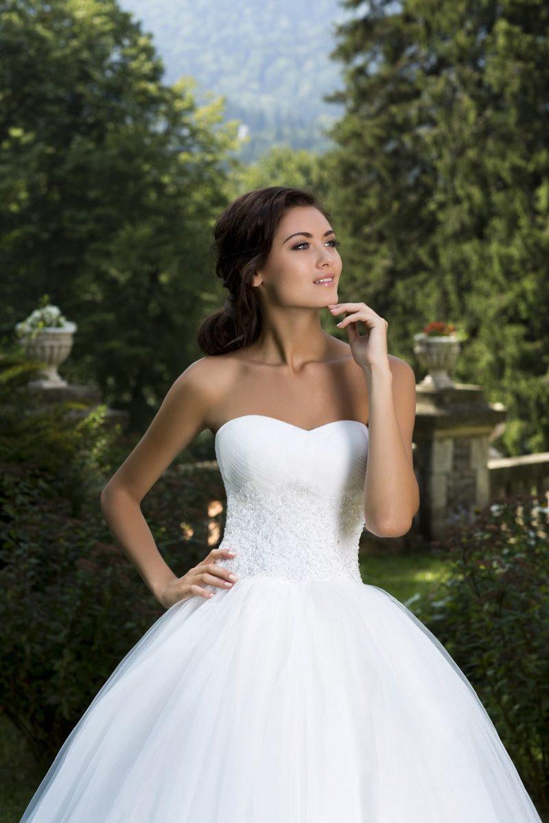 Свадебное платье с изысканным открытым корсетом, украшенным кружевом и драпировками.