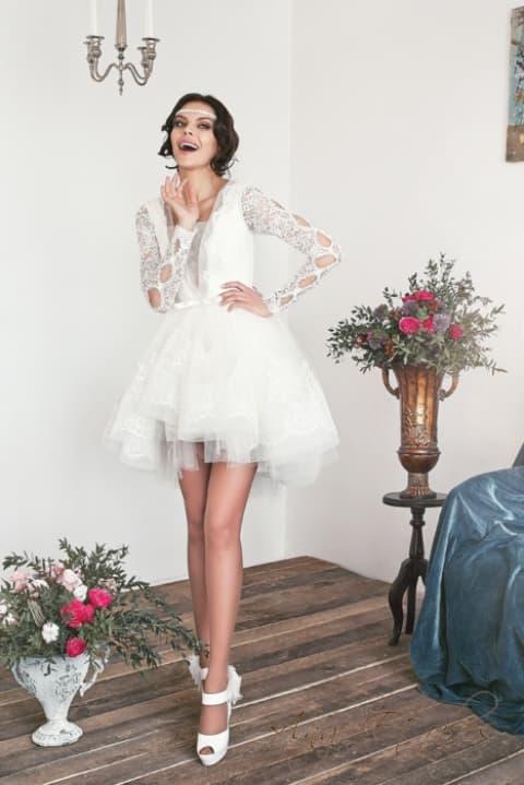 Короткое свадебное платье с невероятно пышной юбкой и длинным рукавом.