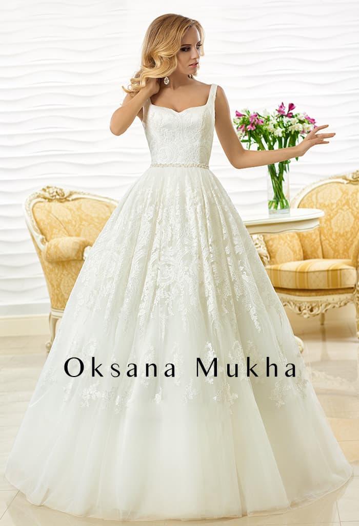 Свадебное платье с фигурным лифом с узкими бретелями и объемной юбкой.