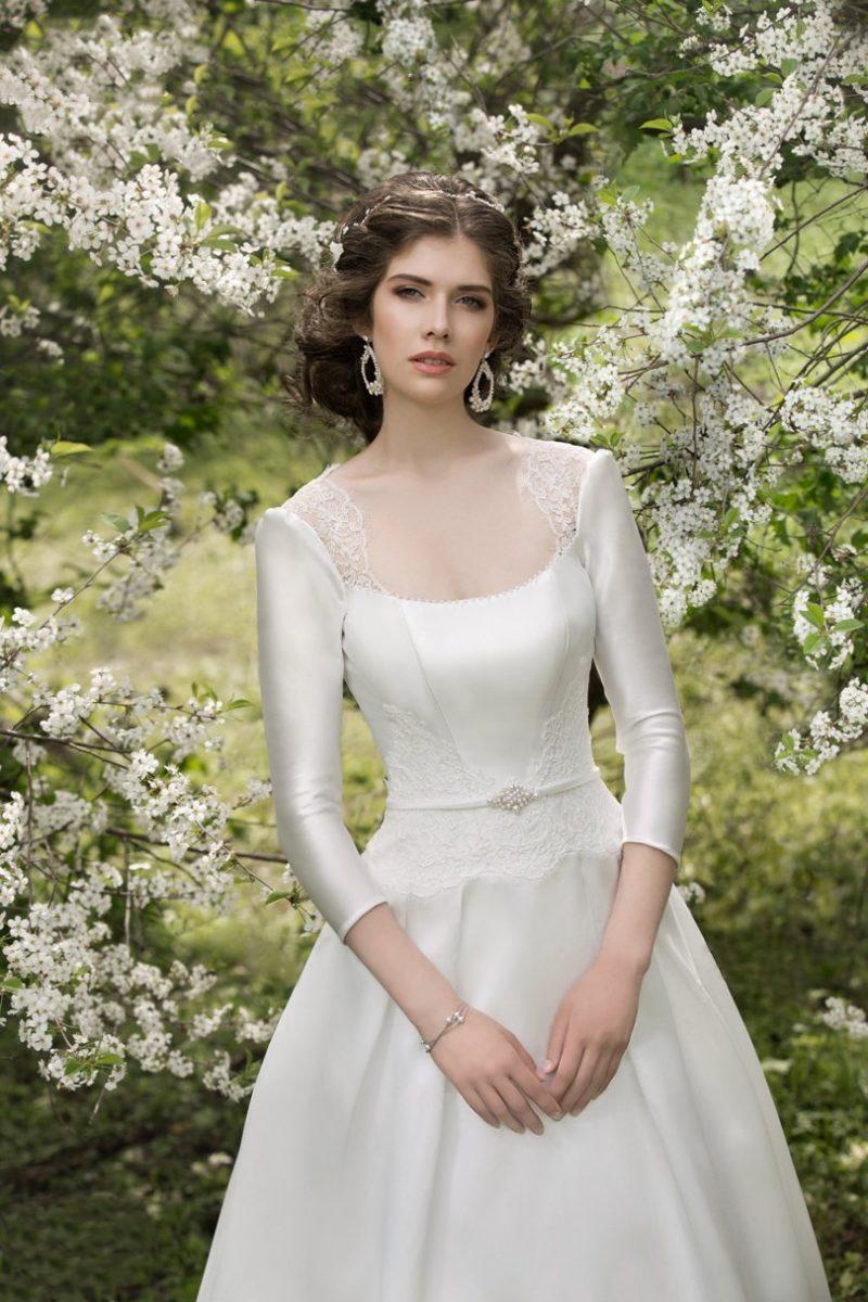Свадебное платье с длинными атласными рукавами и узким поясом на талии.